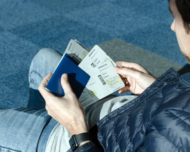 Man with airplane tickets and passport